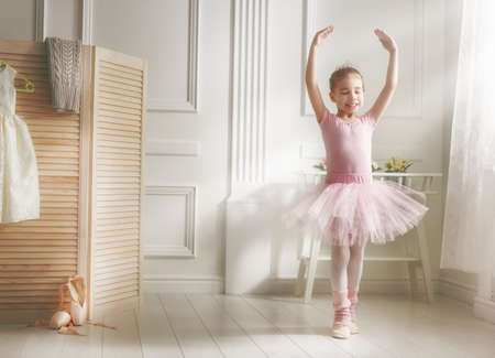 danza: sueños de niña lindo de convertirse en una bailarina. La muchacha del niño en un baile tutú rosado en una habitación. El bebé está estudiando ballet.