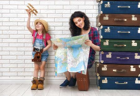 glückliche Familie für die Reise vorbereitet. Mutter und Tochter Blick auf eine Karte und ein Land zu reisen, zu wählen.