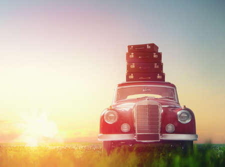 Toward adventure! The suitcases are on the roof of a vintage car.