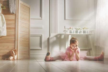 Nettes kleines Mädchen träumt davon, eine Ballerina. Kinder-Mädchen in einem rosa Tutu tanzen in einem Raum. Baby lernt Ballett.