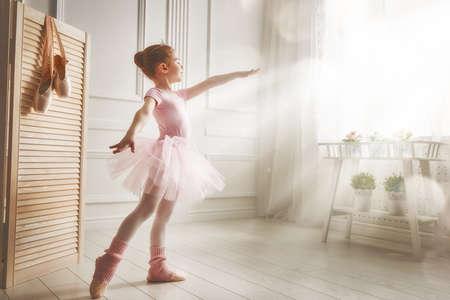 A menina bonito sonhos de se tornar uma bailarina. A menina da criança em uma dança tutu cor de rosa em um quarto. O bebé está estudando ballet.