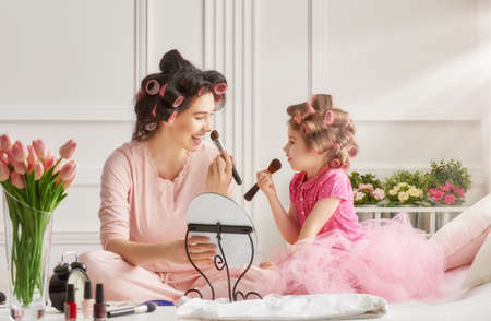 Happy loving family. Mother and daughter are doing hair and having fun. Mother and daughter doing your makeup sitting on the bed in the bedroom. Stock Photo