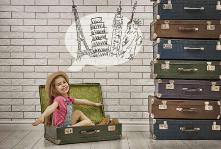 intend: happy child girl against a white brick wall. girl having suitcases and dreaming of traveling.
