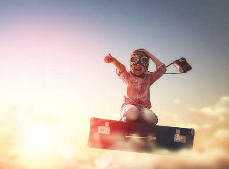 fly: Dreams of travel! Child flying on a suitcase against the backdrop of a sunset. Stock Photo