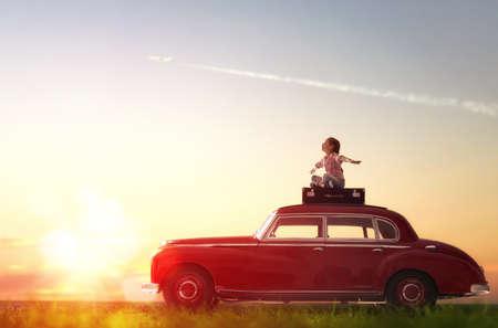 Hacia la aventura! Muchacha que se relaja y disfruta de viaje por carretera. Niña feliz sentado en el techo de los coches de época.