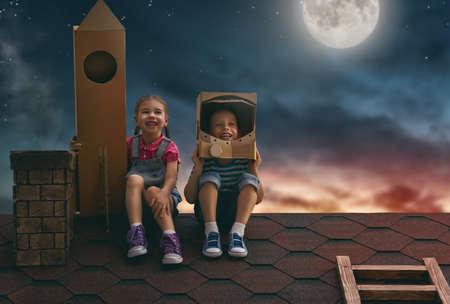 Dos niños pequeños jugando astronautas. Niños en el fondo del cielo de la luna. Muchacho del niño en un traje de astronauta y niña niño con cohete de juguete de pie sobre el techo de la casa y mirando al cielo y el sueño de convertirse en astronautas. Foto de archivo