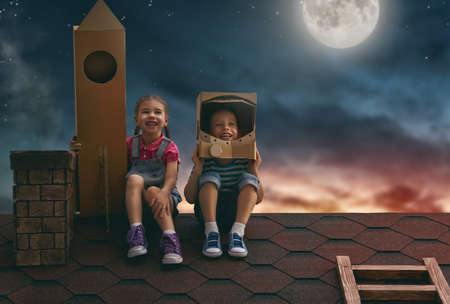 Two little children playing astronauts. Children on the background of moon sky. Child boy in an astronaut costume and child girl with toy rocket standing on the roof of the house and looking at the sky and dreaming of becoming a spacemen. Stock Photo