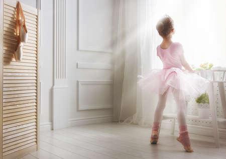 Schattig klein meisje droomt ervan om een ??ballerina. Kind meisje in een roze tutu dansen in een kamer. Meisje van de baby is het bestuderen van ballet. Stockfoto - 55146463