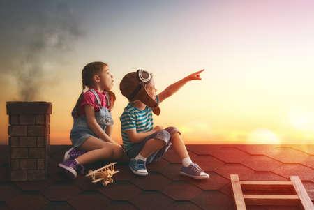dach: Zwei kleine Kinder, die auf dem Dach des Hauses zu spielen und Blick auf den Himmel und träumt von einem Piloten zu werden.