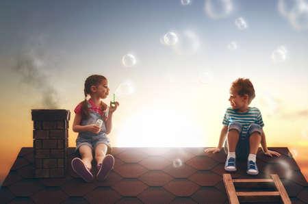 jabon: ¡infancia feliz! chico y chica jugando en el techo. niño soplando burbujas de jabón.