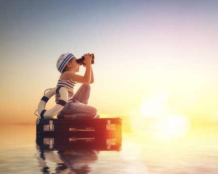 Sueños de viaje! El niño flota en una maleta en el contexto de una puesta de sol. Foto de archivo