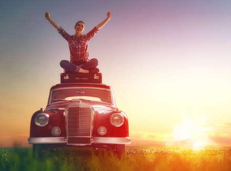 Hacia la aventura! Muchacha que se relaja y disfruta de viaje por carretera. Hermosa mujer joven sentada en el techo del coche de época. Foto de archivo