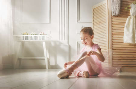 Cute little girl dreams of becoming a ballerina. Child girl in a pink tutu dancing in a room. Baby girl is studying ballet. Stock Photo - 55146763