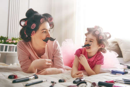 funny girl: Funny family! Mother and her child daughter girl with a paper accessories. Mother and daughter preparing for a party and having fun. Beautiful young woman and funny girl with a paper mustache on stick.