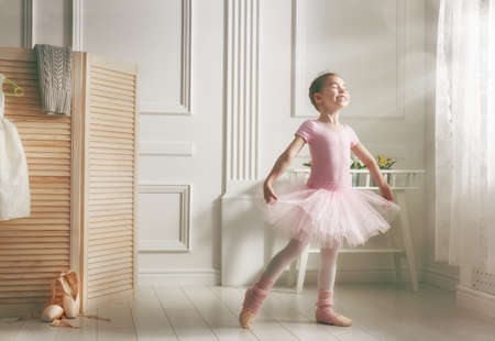 girl shoes: Cute little girl dreams of becoming a ballerina. Child girl in a pink tutu dancing in a room. Baby girl is studying ballet.