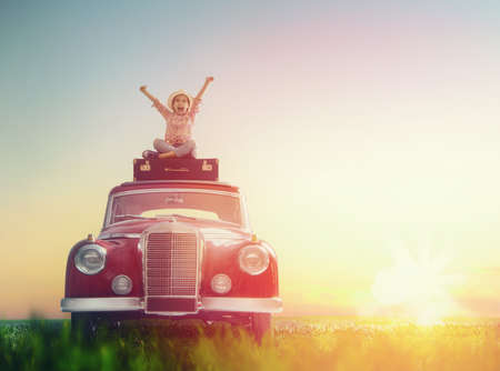 Toward adventure! Girl relaxing and enjoying road trip. Happy child girl sitting on roof of vintage car.