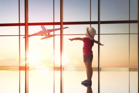 woman sunset: Cute little child girl looks at a plane at the airport.