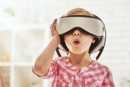 Cute little child girl playing game in virtual reality glasses. Stock Photo