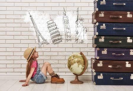 ragazza felice bambino contro un muro di mattoni bianchi. ragazza che ha le valigie e sognando di viaggiare.