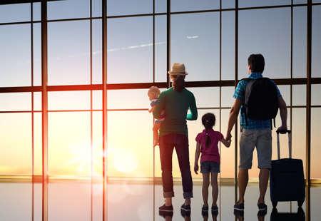 空港で子供たちと幸せな家庭。親と子供たちは、飛行機の窓の外見てください。