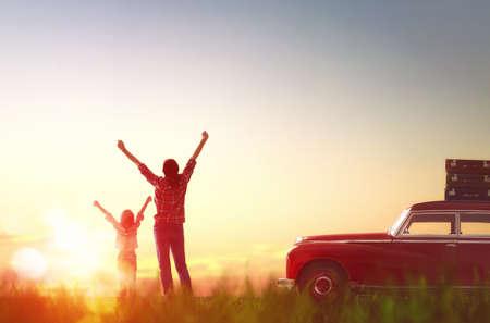 voyage vintage: Vers l'aventure! Happy family détente et profiter de voyage sur la route. Belle jeune mère et sa fille de l'enfant se réjouissent à l'aube. Banque d'images