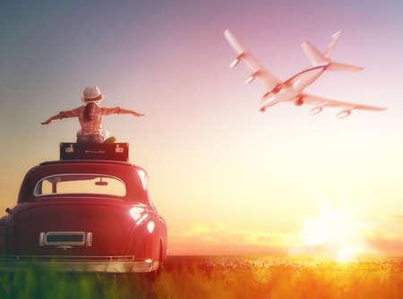 冒険へ!女の子は、リラックスして旅を楽しんでします。幸せな子供の女の子がヴィンテージ車の屋根の上に座って。