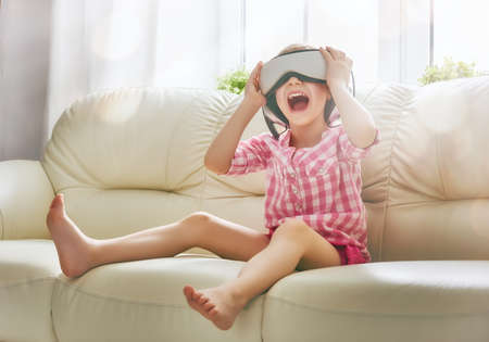 designer baby: Cute little child girl playing game in virtual reality glasses. Stock Photo