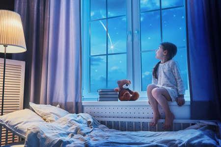 Śliczne dziewczyny dziecko siedzi przy oknie i patrząc na gwiazdy. Dziewczyna podejmowania życzenie widząc spadającą gwiazdę przed snem nocy. Zdjęcie Seryjne
