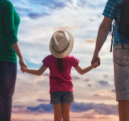 happy family at sunset. mother, father and daughter having fun and playing in nature. family travels. Stock Photo - 56073761
