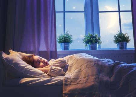 침대에서 자고 사랑스러운 작은 아이 소녀. 조용한 수면 조용한 별이 빛나는 밤.