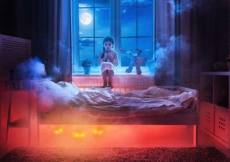 Pesadilla para los niños. Niña niño tiene miedo de los monstruos en la oscuridad de la noche. Asustado niña y su amigo oso de peluche están protegidos contra los monstruos. Foto de archivo