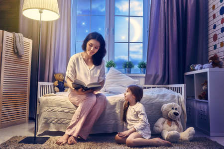 two story: Family reading bedtime. Pretty young mother reading a book to her daughter. Stock Photo