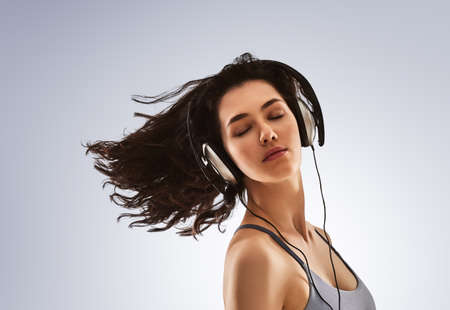 heed: beautiful young woman listening music in headphones on a gray background. the girl is resting and enjoys the music.