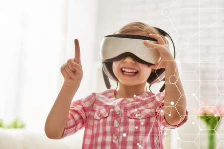Śliczne małe dziecko dziewczyna gra grać w wirtualnych okularów rzeczywistości. Zdjęcie Seryjne