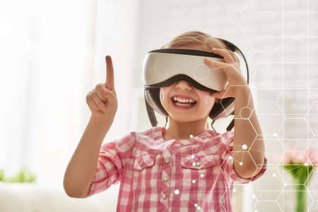 glass house: Cute little child girl playing game in virtual reality glasses. Stock Photo