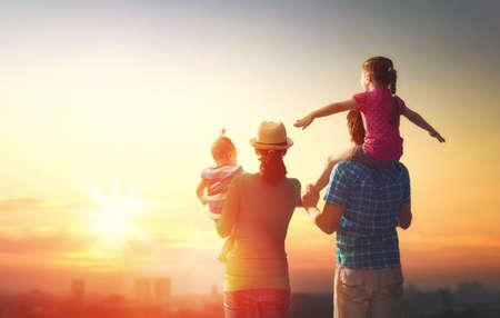 夕暮れ時の幸せな家族。父、母と娘 2 人の子供と自然遊びを楽しんでいます。子供は父親の肩の上に座っています。 写真素材
