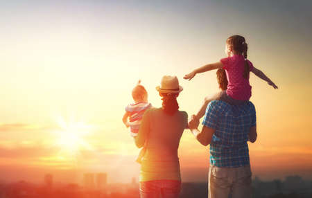 happy family at sunset. father, mother and two children daughters having fun and playing in nature. the child sits on the shoulders of his father. Stock Photo