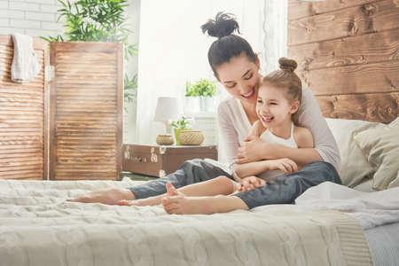 Gelukkig liefdevolle familie. Moeder en haar dochter kind meisje spelen en knuffelen.