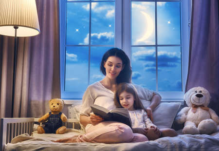 stories: Family reading bedtime. Pretty young mother reading a book to her daughter. Stock Photo