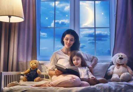 dadã  daughter: Lectura de la familia de acostarse. Bastante joven madre leyendo un libro a su hija.