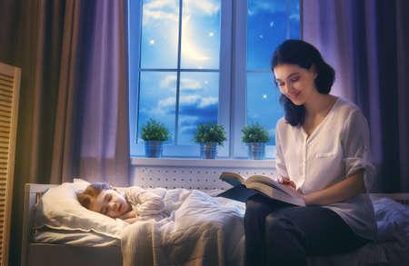 家族読書就寝。かなり若い母親が彼女の娘に本を読んでします。 写真素材