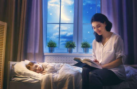 read: Family reading bedtime. Pretty young mother reading a book to her daughter. Stock Photo