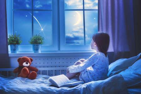 Menina bonito da criança que senta-se na janela e que olha as estrelas. Menina que faz um desejo vendo uma estrela de tiro na noite de dormir. Foto de archivo