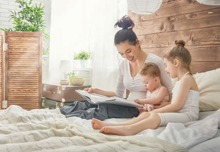 Happy loving family. Pretty young mother reading a book to her daughters. Stock Photo