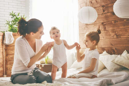 Happy loving family. Mother and her daughters children girls playing in bed. Stockfoto