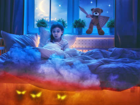 toy story: Nightmare for children. Little child girl is afraid of monsters in the dark of night. Frightened little girl and her teddy bear friend are protected against monsters. Stock Photo