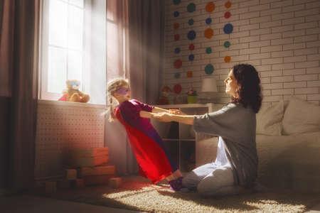 niños riendose: La madre y su niña niño jugando juntos. Muchacha en el traje de un superhombre. Feliz amante de la familia que se divierte. Foto de archivo