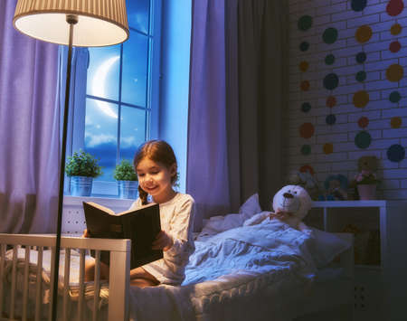 Cute little child girl reading a book under a lamp. Kid girl sitting in her bed on a dark moonlit night. Stock Photo