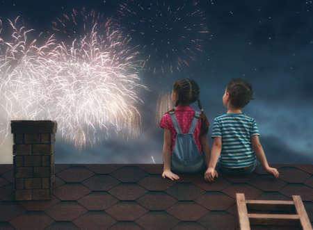 Dos niños lindos que se sientan en el techo y miran los fuegos artificiales.