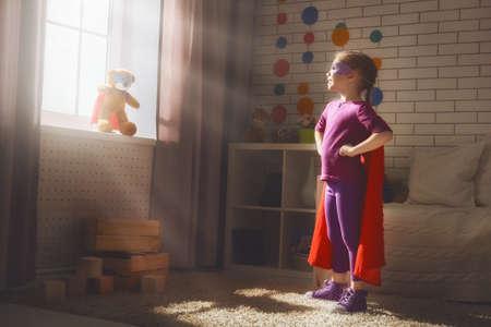 Weinig kind meisje speelt superheld. Kind speelt met haar vriend een teddybeer. Girl power concept. Stockfoto
